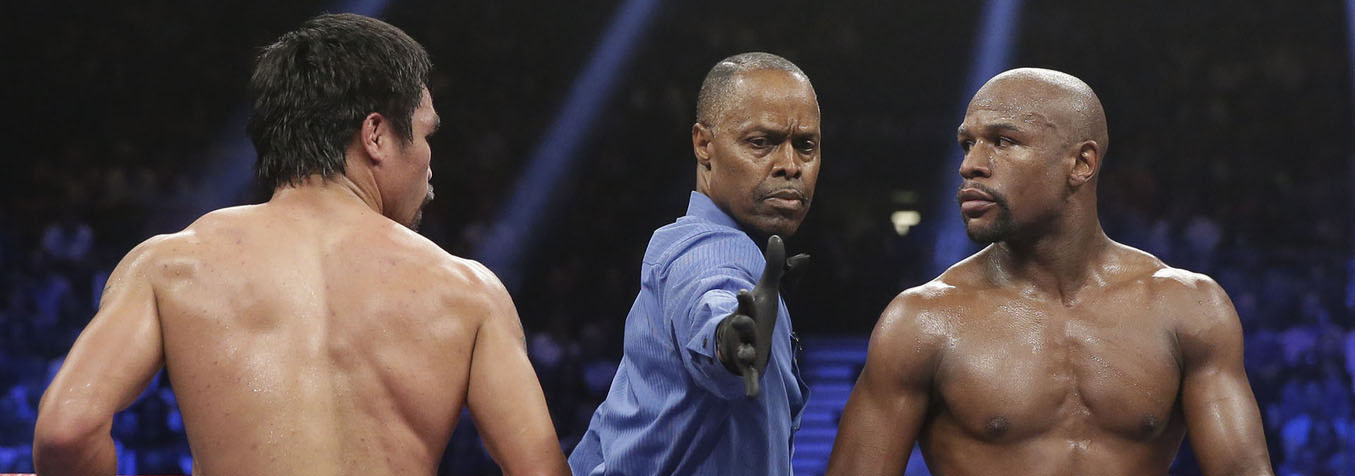 Referee Kenny Bayless separates Manny Pacquiao, from the Philippines, left, and Floyd Mayweather Jr., during their welterweight title fight on Saturday, May 2, 2015 in Las Vegas. (AP Photo/Isaac Brekken)