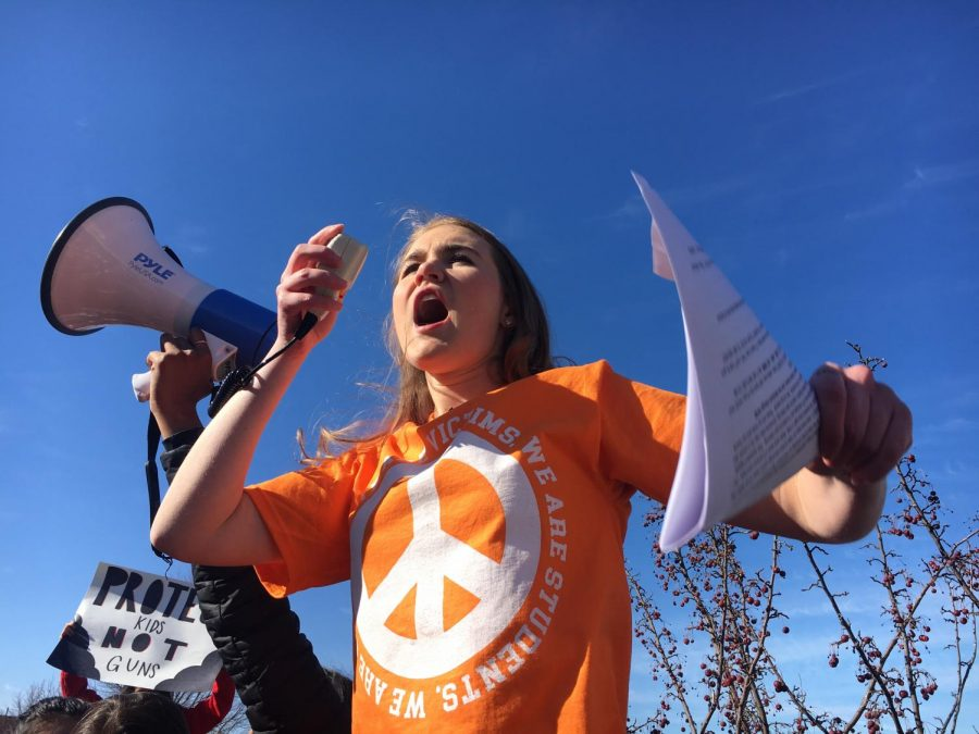 Alexa Jordan, organizer and advocate of the Metea Valley student walkout, projects her voice into a megaphone to gather the attention of the hundreds of students surrounding her.