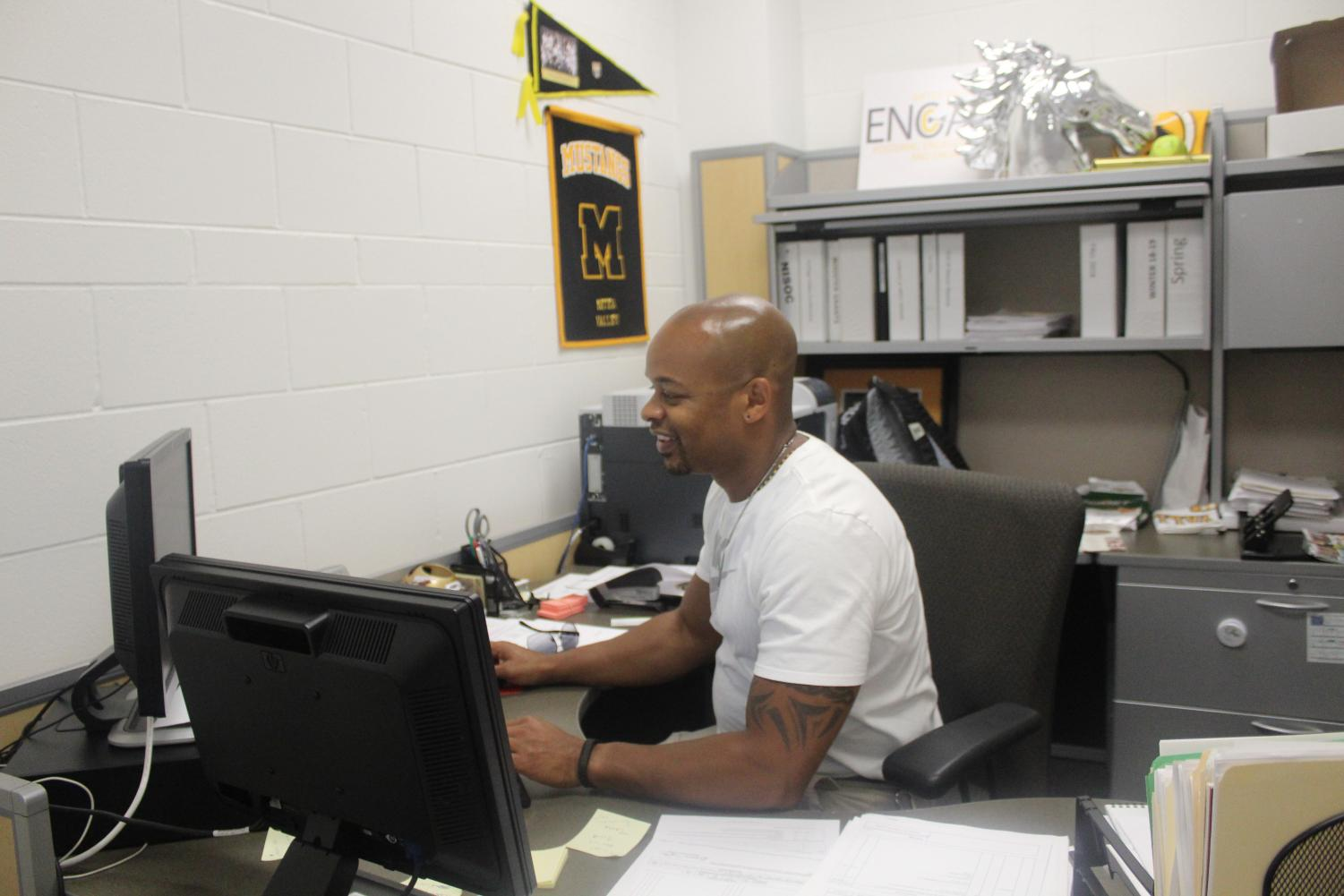 Athletic Director Jason Ward works at his desk to plan and transition teams from summer practices to competition season.