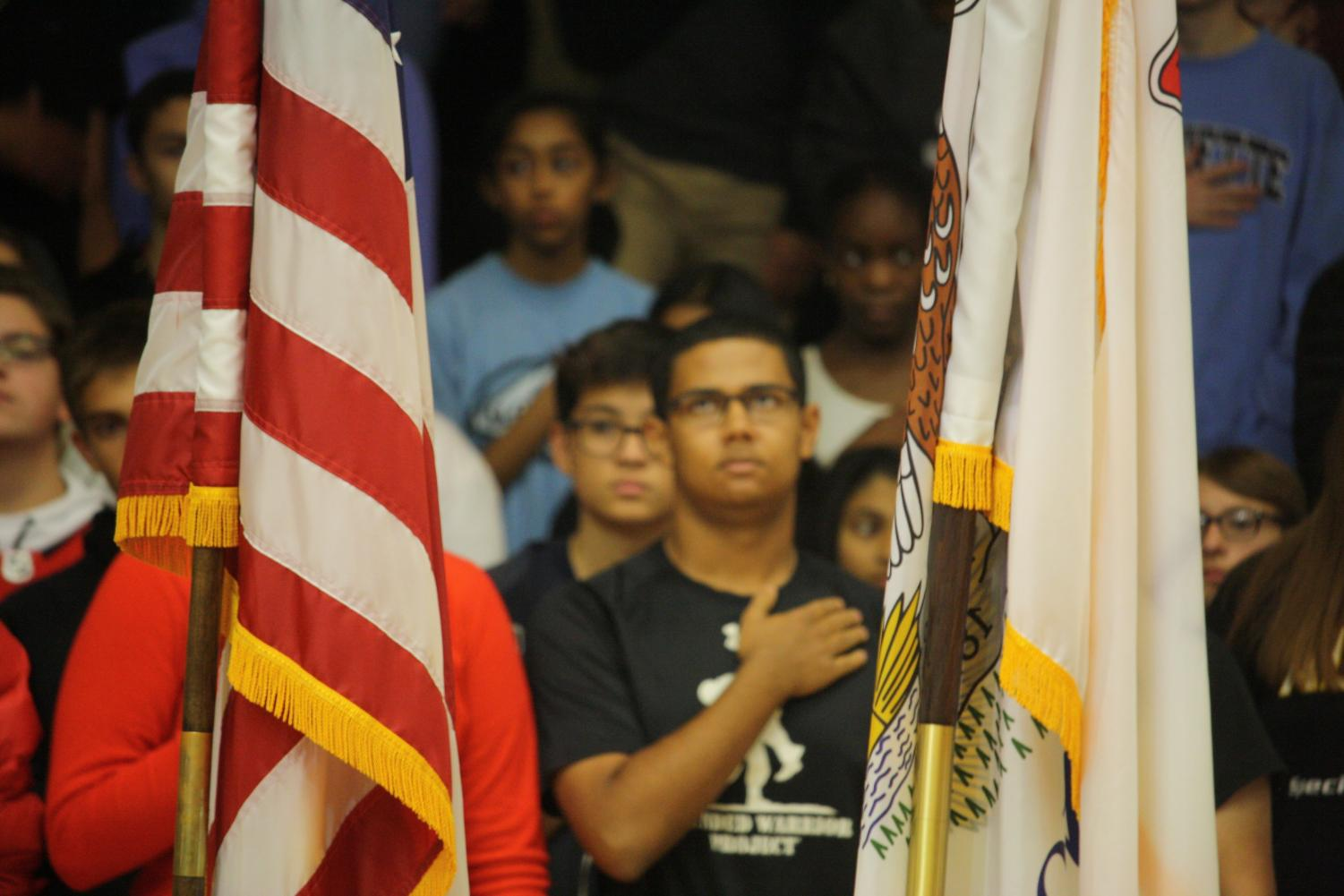Students+stand+and+pay+their+respects+to+the+American+flag