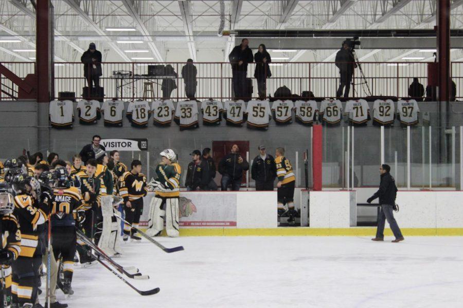 Seniors' jerseys displayed above team benches.