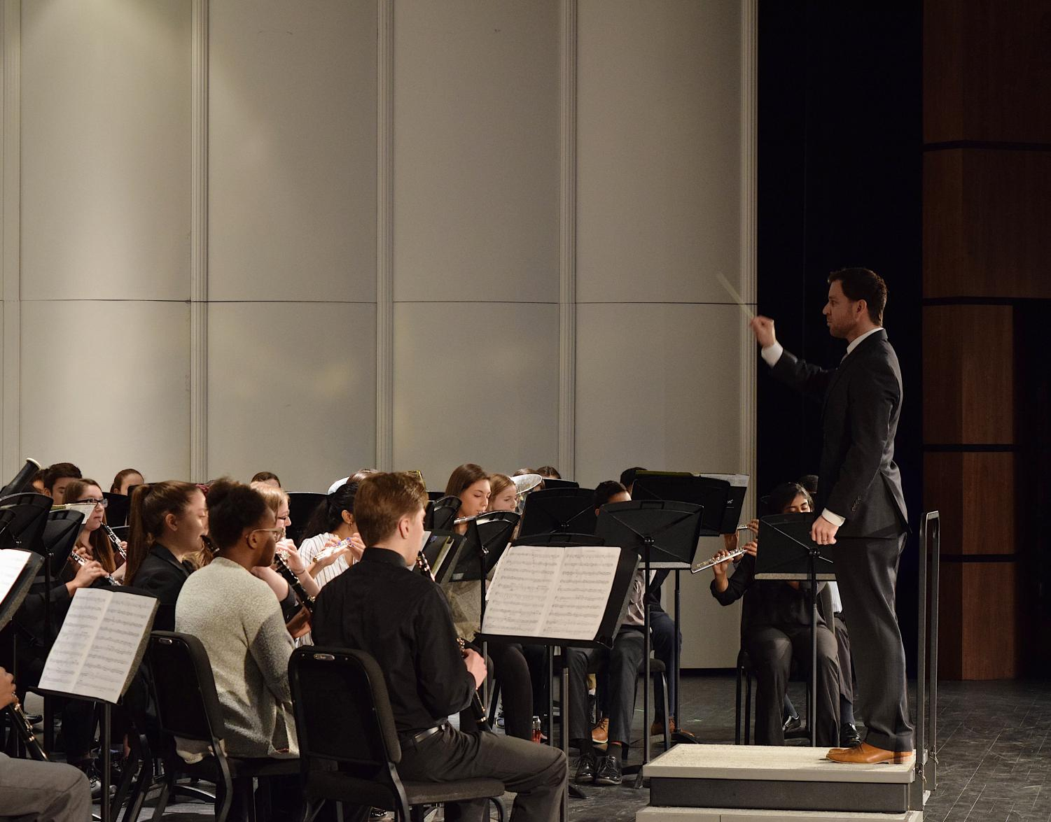 Mr.+Kaminsky+conducting+the+band+as+the+students+are+focused+on+the+notes.