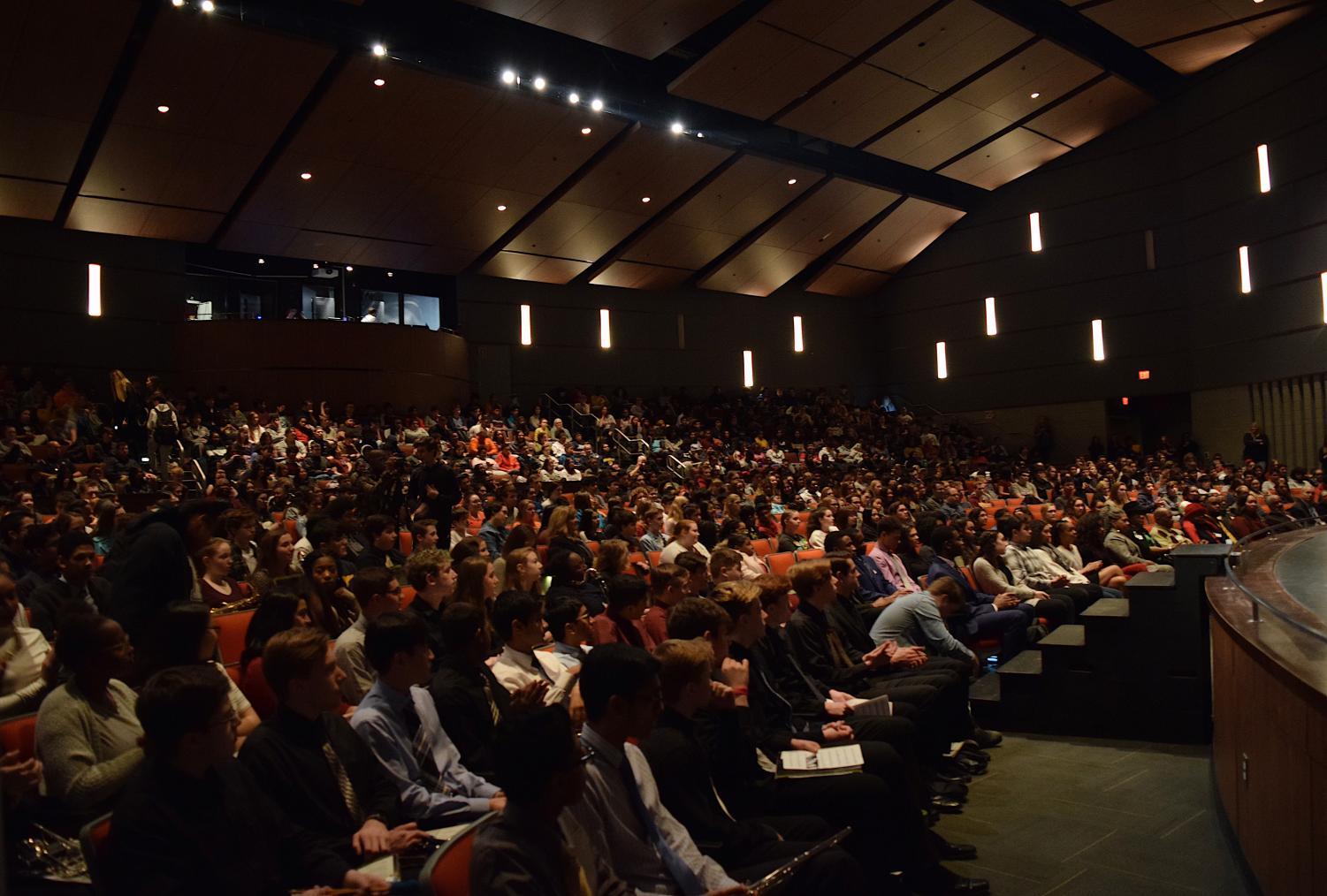 With+a+full+auditorium%2C+students+sit+respectfully+in+silence.