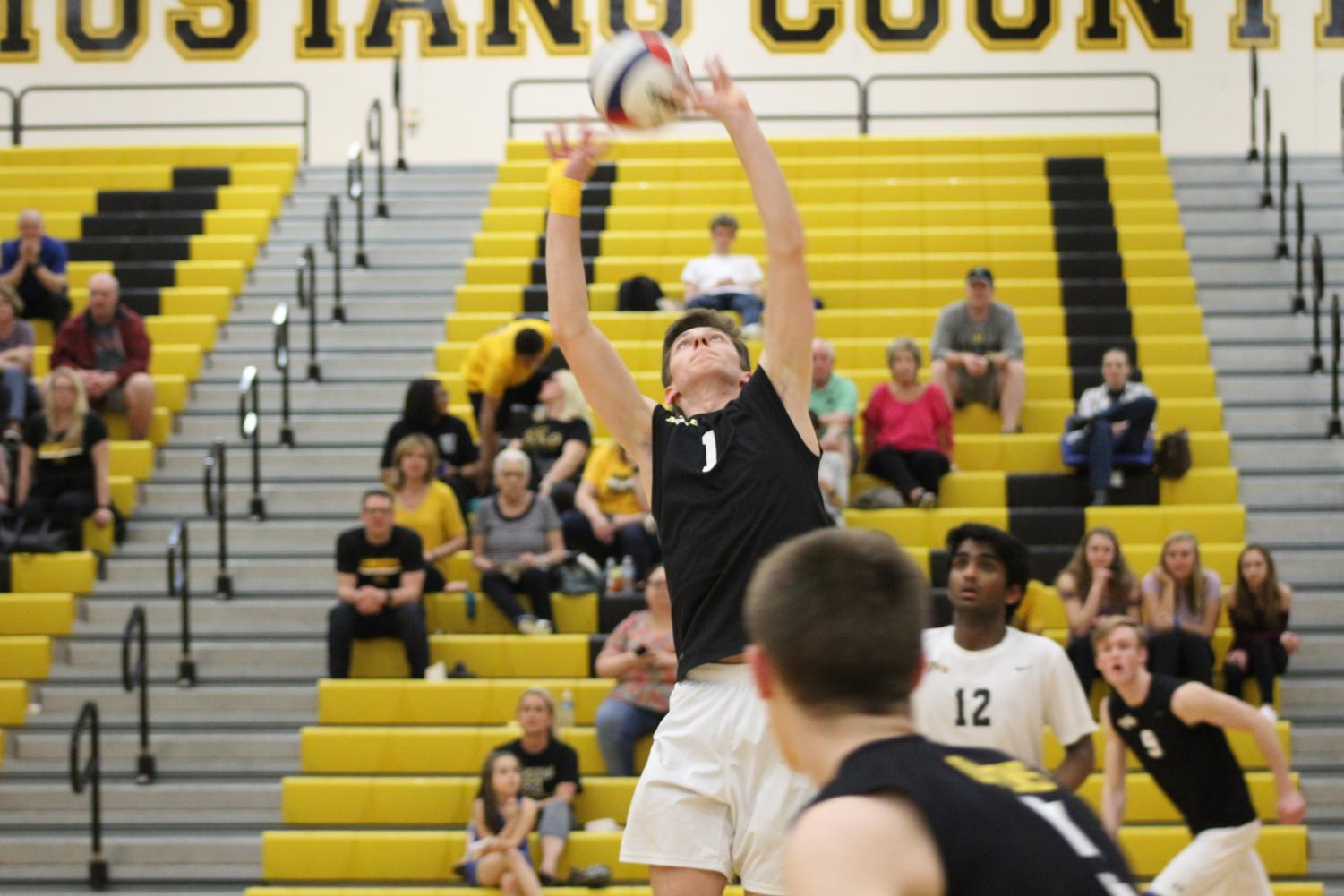 Junior setter Brandon Long setting the ball to teammate and outside hitter Ryan Owens during the conference opener game against Naperville Central on April 15.