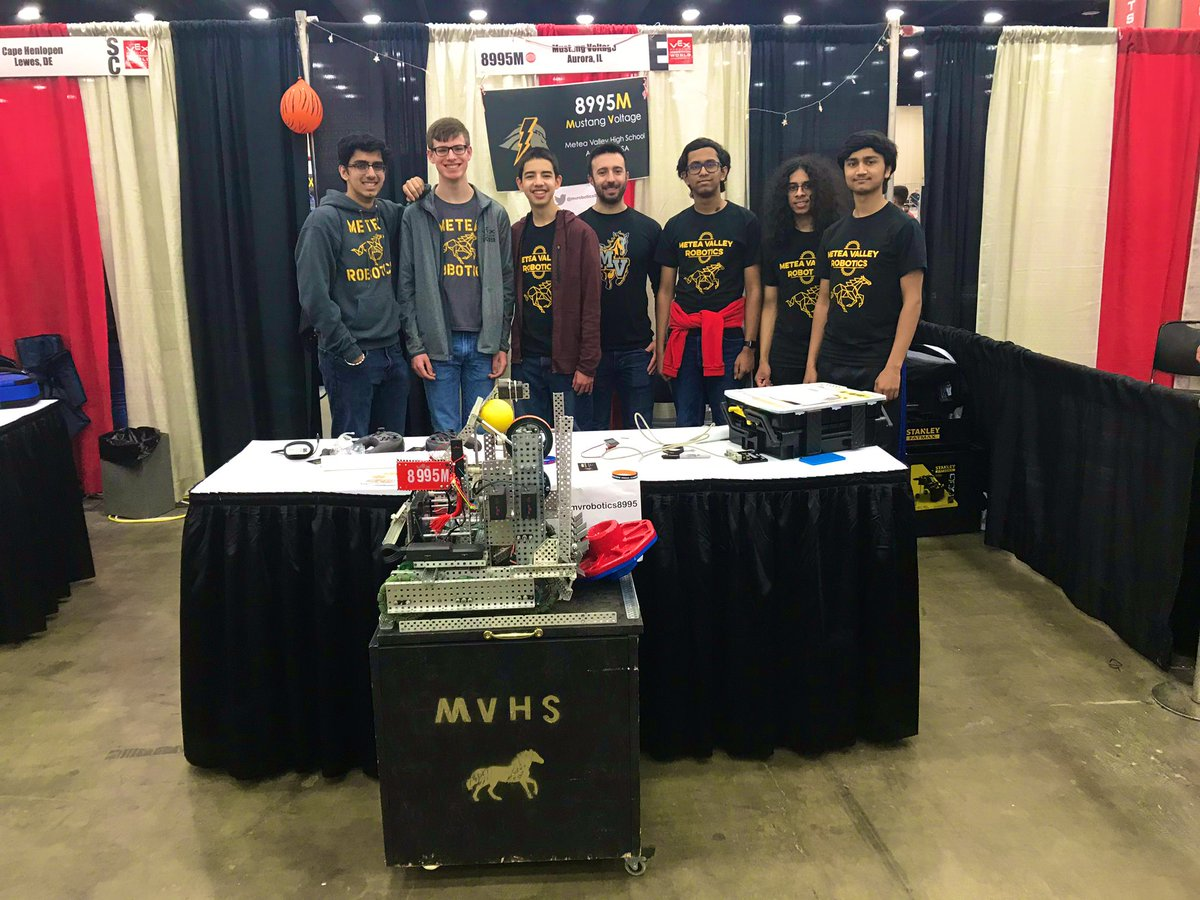 The team and Coach Romeo show off their robot at their booth.The team poses at their booth. From left: Rohit Tuteja, Sam Hus, Nathan Pruyne, Coach Romeo, Shri Bellala, Jim James, Archit Chabbi