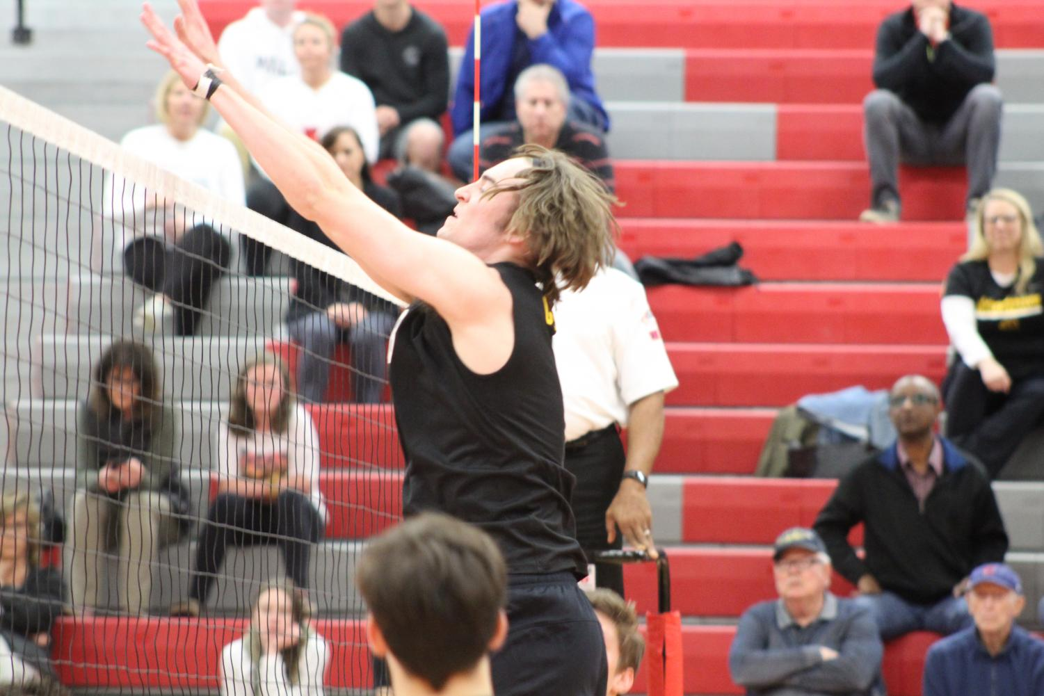 Senior+and+middle+hitter+Alec+Gaertner+blocks+the+ball+during+the+first+set+of+the+night.