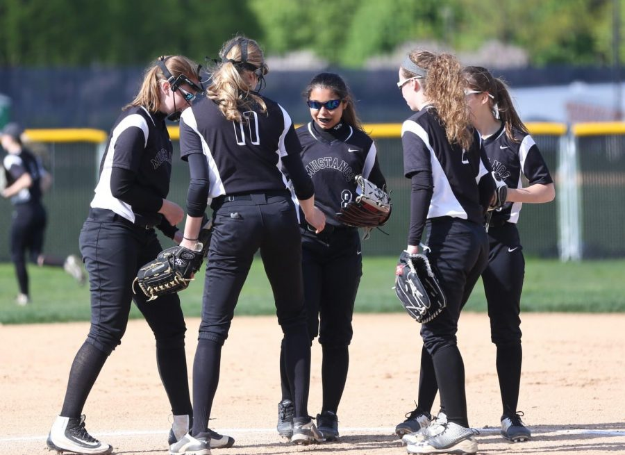 The girls softball team huddle together during the second inning on May 3rd against Naperville North.