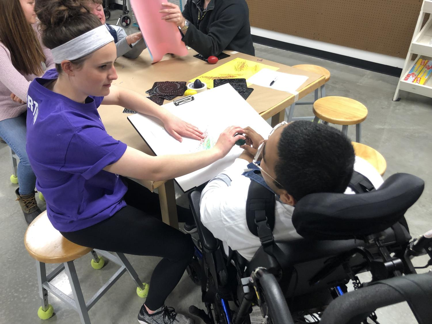 Students work on an art piece during a trial of the adaptive art class