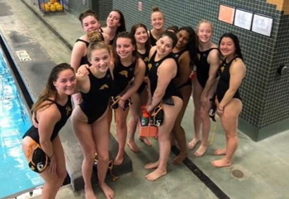 The girls' water polo team pose for a picture together.