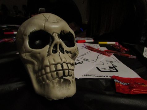 Twizzlers, coloring pages, and skulls decorate the table.