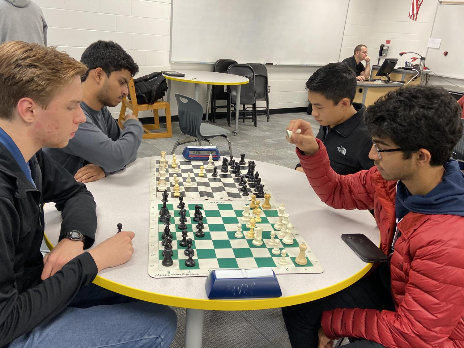 Chess  team members practice matches to prepare for their meets.