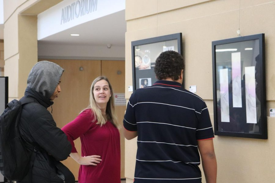 Students and staff admire artwork displayed outside the auditorium.