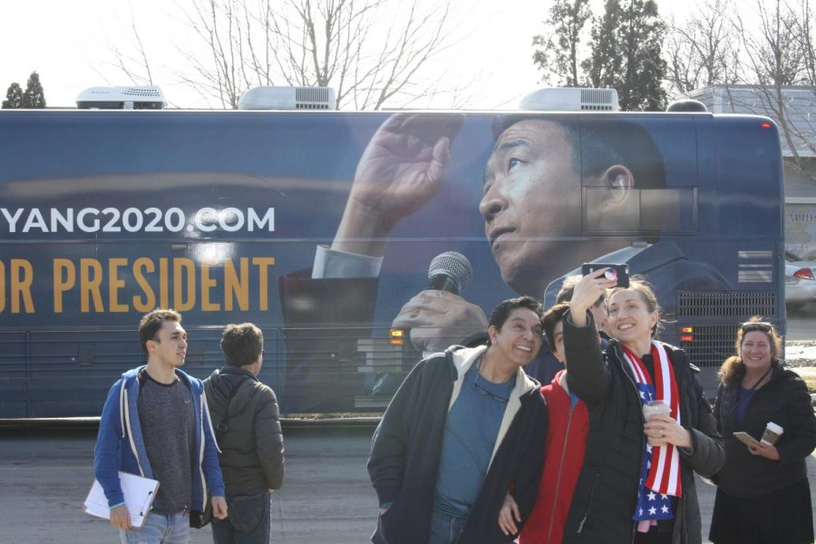 Office visitors capture a shot of themselves in front of Andrew Yangs tour bus.