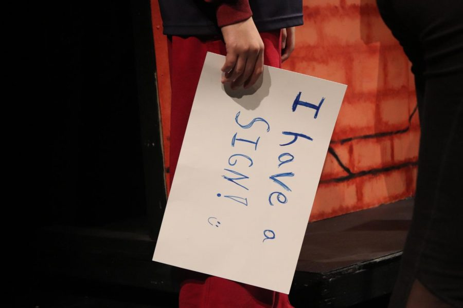 Drew Chandler holds a sign between sketches.