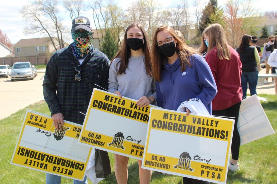 Students receive their graduation yard signs.