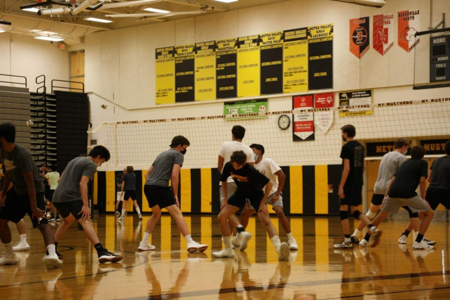 The boys' volleyball team start their warm ups with stretches.